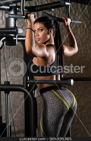 Latino Woman Doing Exercise For Back stock photo, Sexy Latino Woman Working Out Back On Machine In Fitness Center by Jasminko Ibrakovic