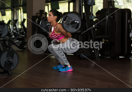 Latino Woman Doing Exercise Barbell Squat stock photo, Sexy Latino Woman Working Out Legs With Barbell In Fitness Center - Squat by Jasminko Ibrakovic