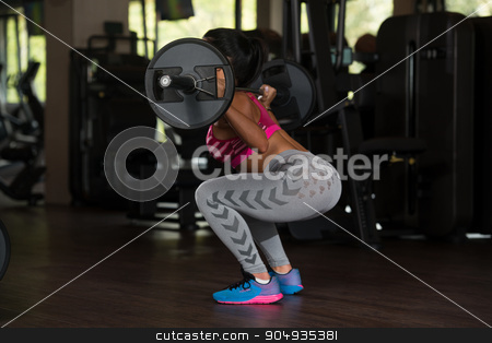 Latino Woman Doing Heavy Weight Exercise For Back stock photo, Young Mexican Woman Working Out Legs With Barbell In Fitness Center - Squat by Jasminko Ibrakovic