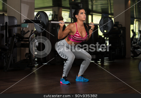 Latin Woman Doing Exercise Barbell Squat stock photo, Young Mexican Woman Working Out Legs With Barbell In Fitness Center - Squat by Jasminko Ibrakovic
