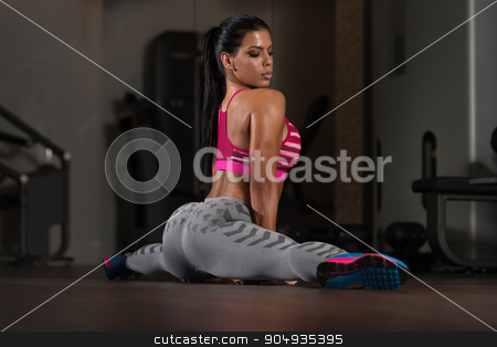 Young Fitness Woman Stretching On The Floor stock photo, Young Woman Doing Stretching Exercises On The Floor At The Gym by Jasminko Ibrakovic
