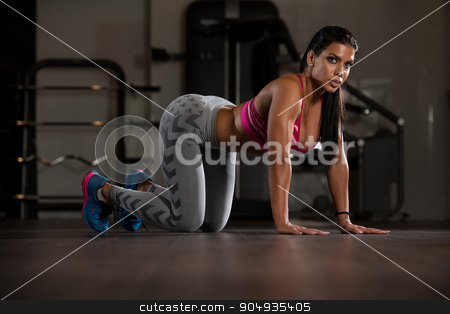 Portrait Of Young Woman Doing Stretching Exercise stock photo, Young Woman Doing Stretching Exercises On The Floor At The Gym by Jasminko Ibrakovic