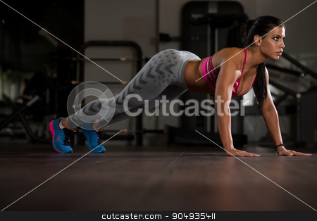 Young Woman Doing Push Ups On Floor stock photo, Young Woman Athlete Doing Pushups As Part Of Bodybuilding Training by Jasminko Ibrakovic