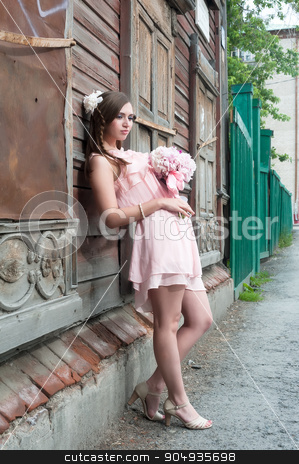 beautiful woman with flower near old wooden house stock photo, Portrait of a beautiful brunette woman with peony flowers near old wooden abandoned house by Aikon