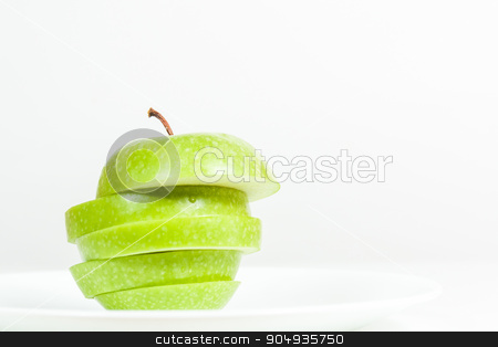 Slices of green apple in a  plate stock photo, Slices of green apple in a white plate  by Robinson Thomas