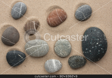 striped stones lying on the sand stock photo, striped stones lying on the sand by alekleks