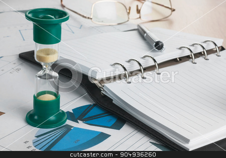 Hourglass, diary, glasses and pen stock photo, Hourglass, diary, glasses and pen lying on a background of diagrams and graphs  by alekleks
