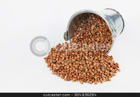 Buckwheat grains spilling out of bucket stock photo, Buckwheat grains spilling out of bucket, on a white background by alekleks