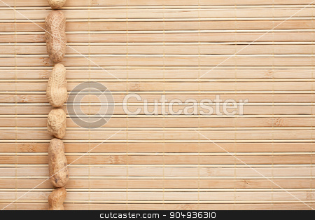 Unrefined peanuts lying on a bamboo mat  stock photo, Unrefined peanuts lying on a bamboo mat can be used as background by alekleks