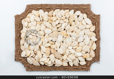 Figured frame of burlap with pumpkin seeds stock photo, Figured frame of burlap with pumpkin seeds, on a white background by alekleks