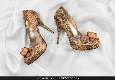 High-heeled shoes  lying on white  fabric stock photo, High-heeled shoes  lying on white  fabric, can use as background by alekleks