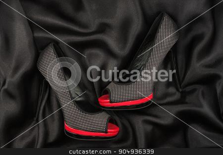 High-heeled shoes lying on black  fabric stock photo, High-heeled shoes lying on black  fabric, can use as background by alekleks