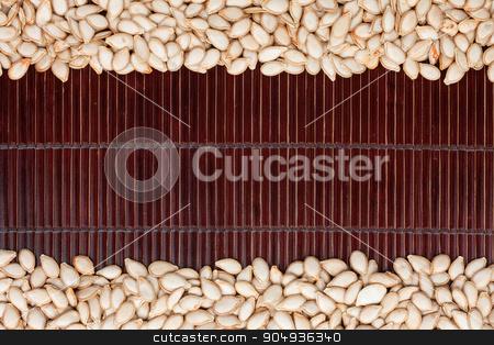 pumpkin seed  on a dark  bamboo mat stock photo, pumpkin seed  on a dark  bamboo mat, with space for text by alekleks