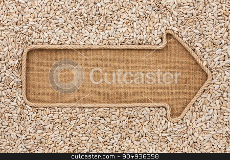 Pointer made from rope with  sunflower seeds  lying on sackcloth stock photo, Pointer made from rope with  sunflower seeds  lying on sackcloth, with space for your text by alekleks