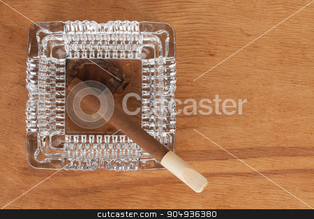 Glass ashtray with cigar stands on a wooden surface stock photo, Glass ashtray with cigar stands on a wooden surface, can be used as background by alekleks