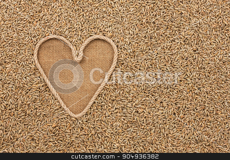 The symbolic heart made of rope lies on sackcloth and rye grains stock photo, The symbolic heart made of rope lies on sackcloth and rye grains, with space for your text by alekleks