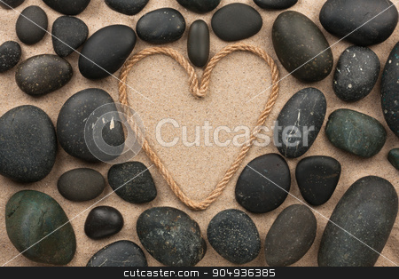 Beautiful frame of rope in the form of heart with black stones stock photo, Beautiful frame of rope in the form of heart with black stones, on the sand by alekleks