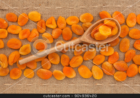 Wooden spoon with  dried apricots   stock photo, Wooden spoon with  dried apricots,  lying on sackcloth by alekleks