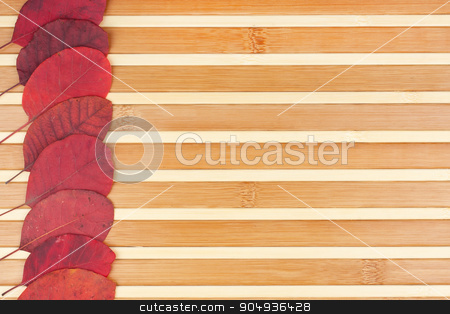 Red autumn leaves lying on a bamboo mat stock photo, Red autumn leaves lying on a bamboo mat, can be used as background  by alekleks