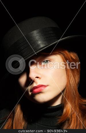 Portrait of a beautiful girl in a black hat stock photo, Portrait of a beautiful girl in a black hat, on black background by alekleks