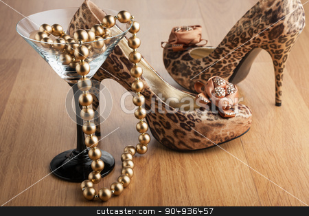 Gold beads in a martini glass stock photo, Gold beads in a martini glass on the background of  leopard shoes by alekleks