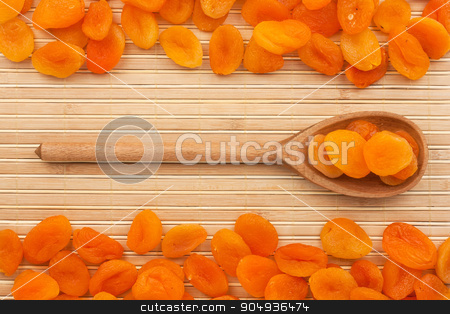 Wooden spoon with  dried apricots   stock photo, Wooden spoon with  dried apricots   lying on bamboo  mat by alekleks