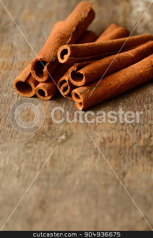 Bunch of cinnamon sticks stock photo, Bunch of cinnamon sticks on a wooden background by sutike