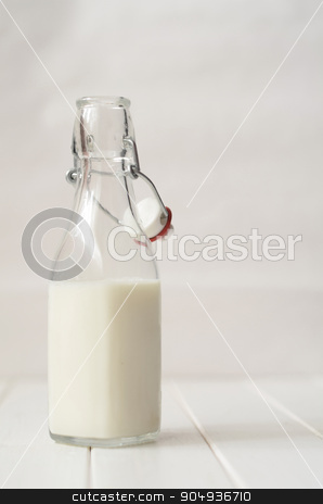 Milk in a glass bottle stock photo, Milk in a glass bottle on white wooden background by sutike
