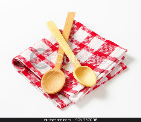 Checked tea towel and wooden spoons stock photo, Red and white tea towel and wooden spoons by Digifoodstock