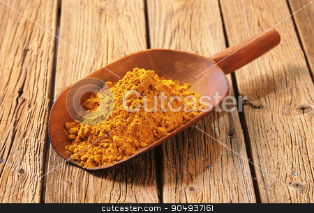 Curry powder stock photo, Heap of curry powder on a wooden scoop by Digifoodstock