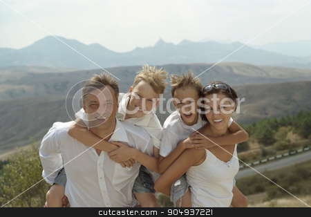 Happy family near mountains stock photo, Happy family posing near mountains in summer by Ruslan Huzau