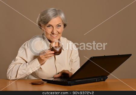 Old woman with  laptop and coffee stock photo, Old woman with a laptop and coffee on  background by Ruslan Huzau