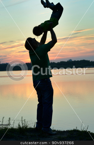Father and son playing on the beach  stock photo, Father and son playing on the beach at the sunset time by Ruslan Huzau