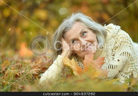 senior woman in  autumn park stock photo, Happy beautiful senior woman in the autumn park by Ruslan Huzau