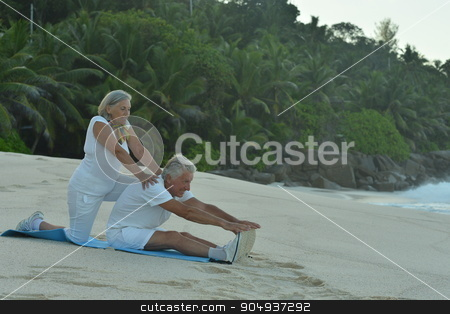 Senior couple exercising  in summer stock photo, Happy Senior couple exercising in summer on  seashore by Ruslan Huzau