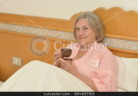 Senior woman in bedroom with  coffee stock photo, Senior woman in bedroom with cup of coffee by Ruslan Huzau