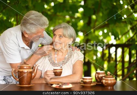 Couple drinking tea stock photo, Senior Couple drinking tea in summer garden by Ruslan Huzau