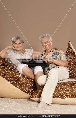 Senior couple sitting with laptop stock photo, Portrait of Senior couple sitting with laptop by Ruslan Huzau