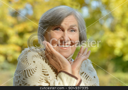 Happy elderly woman  stock photo, Happy elderly woman enjoying in autumn park by Ruslan Huzau
