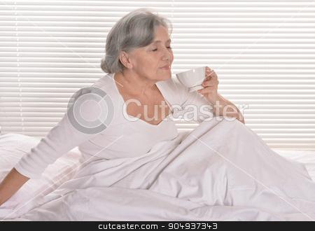 Senior woman in bedroom with coffee stock photo, Senior woman in bedroom with cup of coffee by Ruslan Huzau