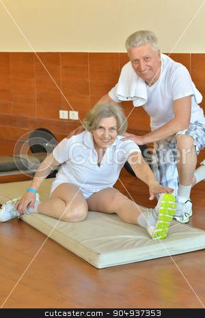 senior couple exercising in gym stock photo, Active smiling senior couple exercising in gym by Ruslan Huzau