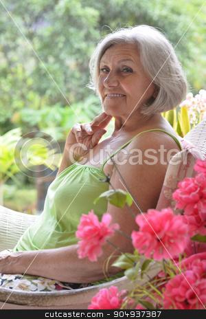 Older woman with flowers stock photo, Portrait of a beautiful older woman with flowers by Ruslan Huzau
