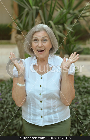 senior woman in near hotel stock photo, Portrait of a senior woman on a walk near hotel at tropic resort with hands up by Ruslan Huzau