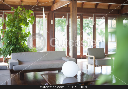 Bright living room with big windows  stock photo, Bright living room with a beige sofa, coffee table with sphere illuminator, some house plants and big windows by JRstock