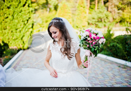 Cinderella bride with bouquet looking down stock photo, Cinderella bride with bouquet looking down by Andrii Shevchuk
