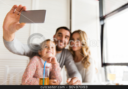 close up of family taking selfie at restaurant stock photo, family, parenthood, technology and people concept - close up of happy mother, father and little girl having dinner and taking selfie by smartphone at restaurant by Syda Productions