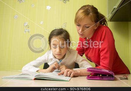 Beautiful school girl doing homework with sexy mother at home stock photo, Beautiful school girl doing homework with mother at home by Kopytin Georgy