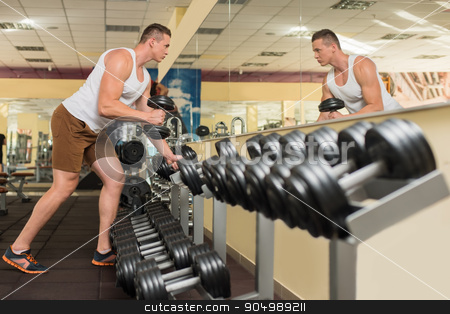 Young sportsman in gym. stock photo, Young guy in gym. Sportsmen standing at the mirror in gym. Guy taking dumbbells and looking at the mirror. by Denys