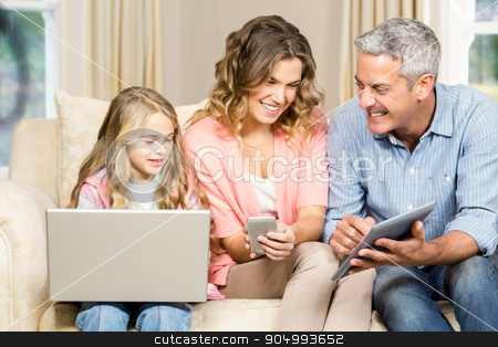 Happy family using laptop, tablet and smartphone stock photo, Happy family using laptop, tablet and smartphone at home by Wavebreak Media
