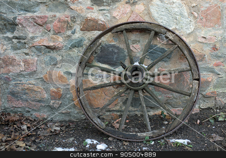 Old wooden wagon wheel stock photo, Old wooden wagon wheel on a stone wall in winter by Harry Huber